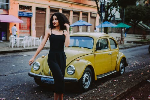 Woman Walks Behind Yellow Volkswagen Beetle