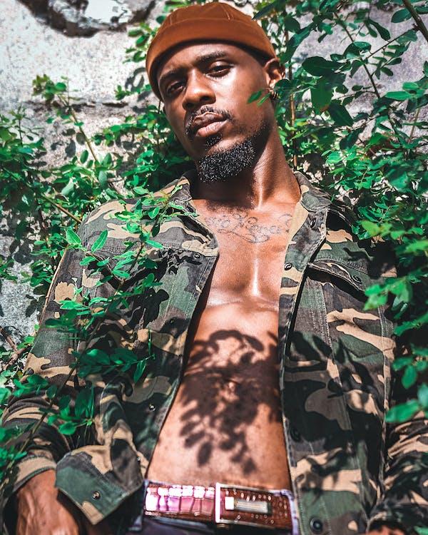 植物と灰色の壁に寄りかかって茶色、緑、黒のカモフラージュジャケットを着ている男