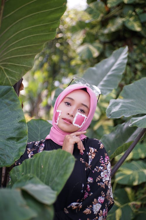Photo of Woman in Pink Hijab Posing by Green Taro Plants