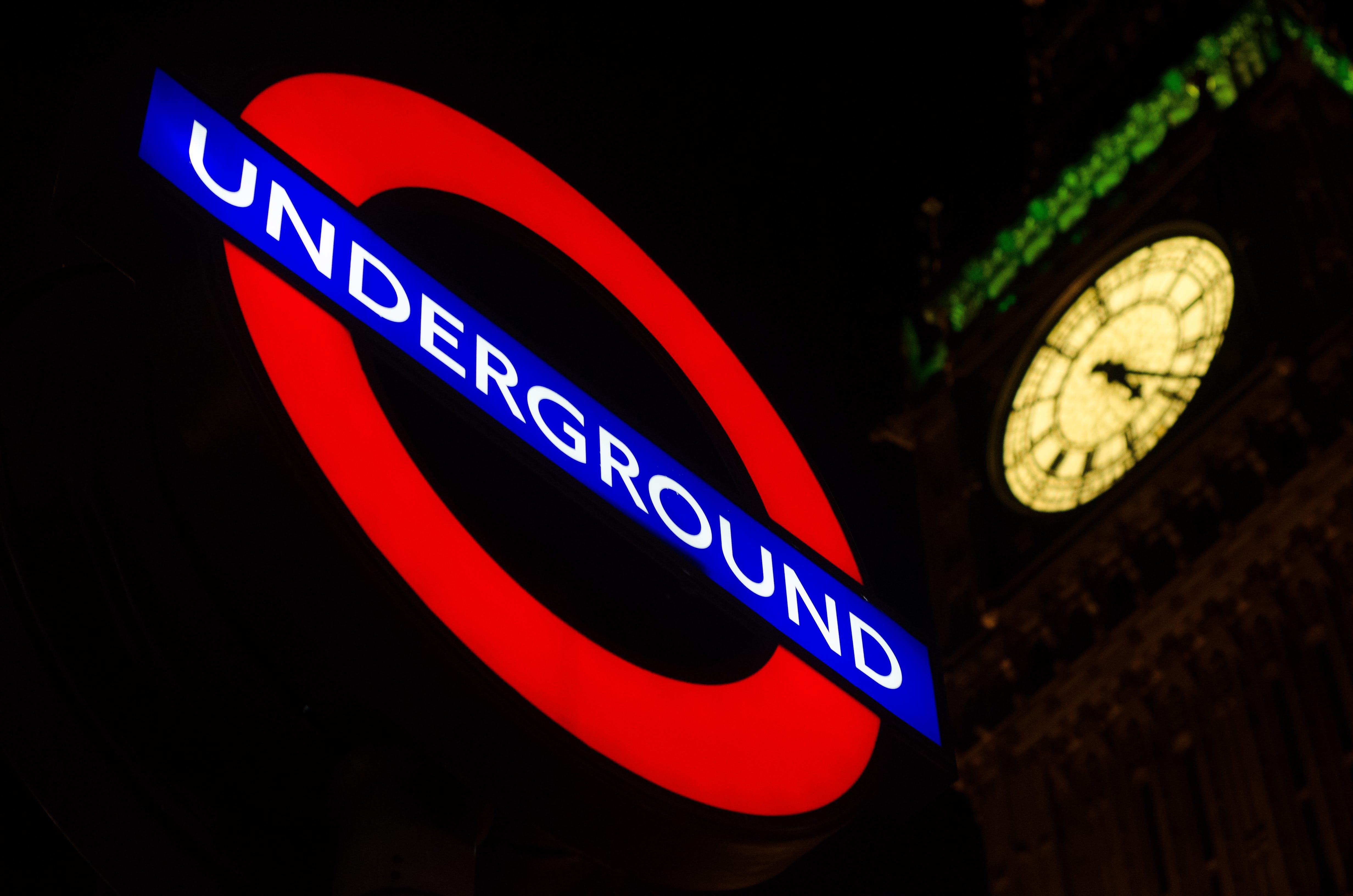 Underground Signage Near Clock Tower during Night
