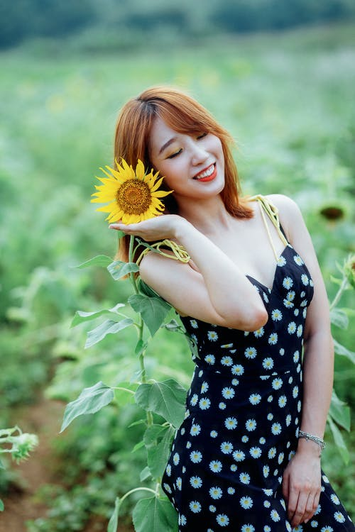 Selective Focus Photo of Smiling Woman in Black Floral Dress Posing Next to Sunflower With Her Eyes Closed