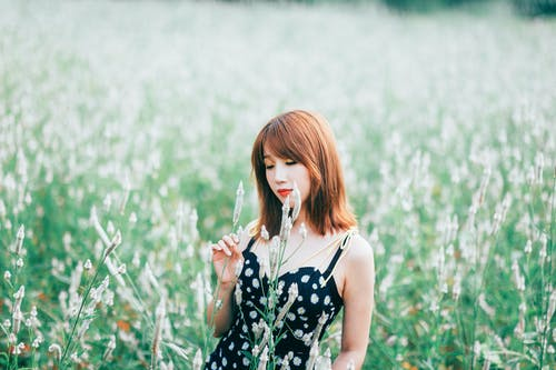 Selective Focus Photo of Woman in Black Floral Dress Standing Alone in Grass Field Posing With Her Eyes Closed