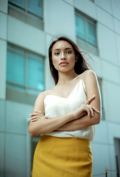Selective Focus Photo of Woman in White Top and Yellow Skirt Posing Outside Building With Her Hands Crossed
