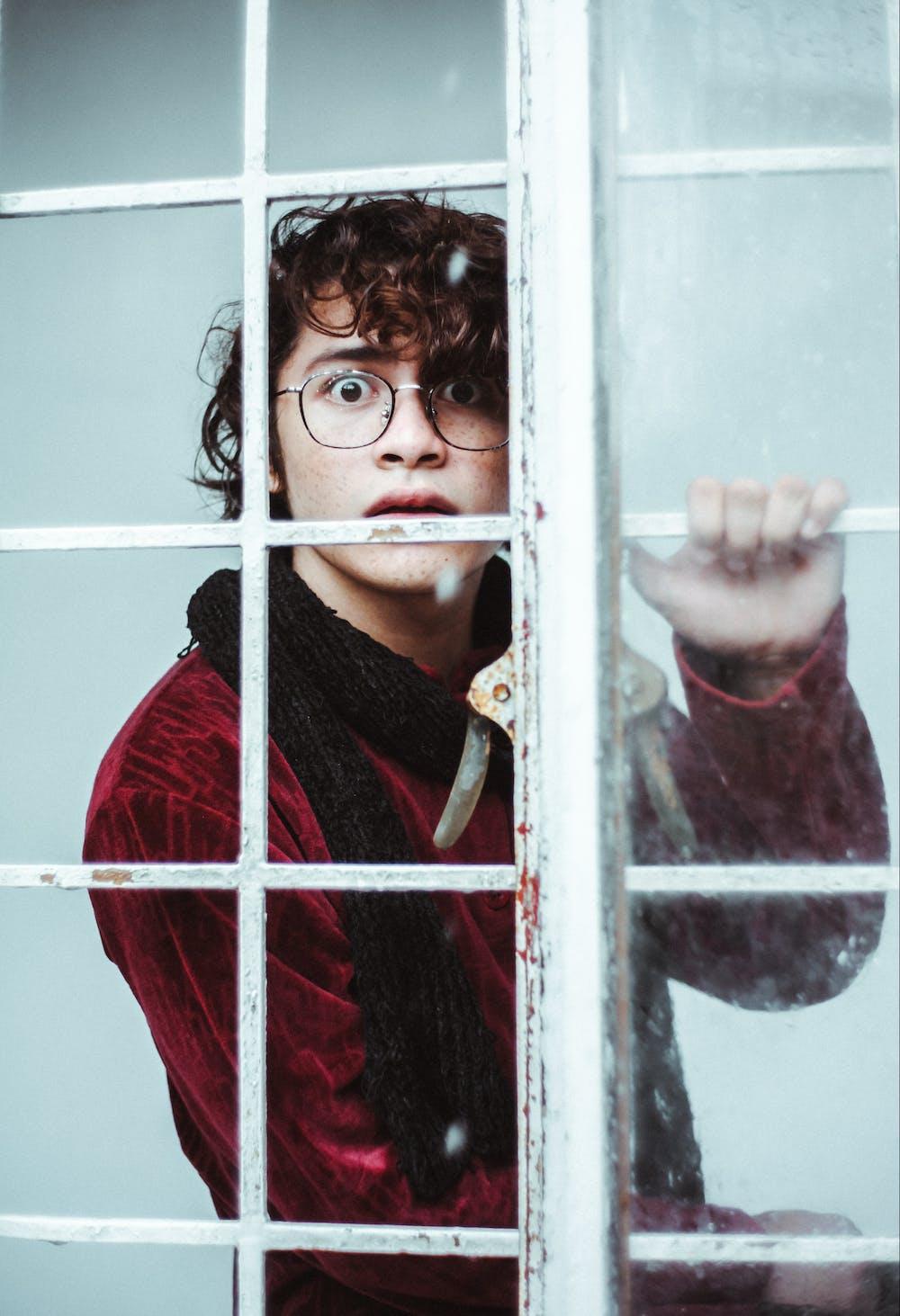 A man standing near window pane. | Photo: Pexels