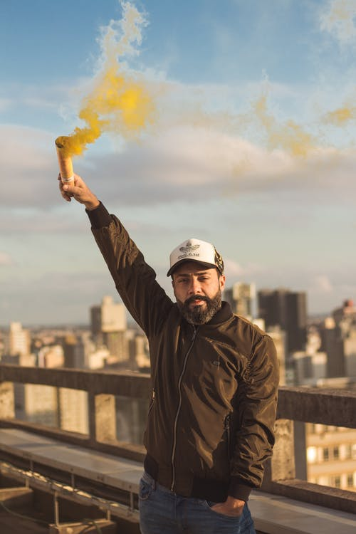 Man Holding Yellow Smoke Bomb