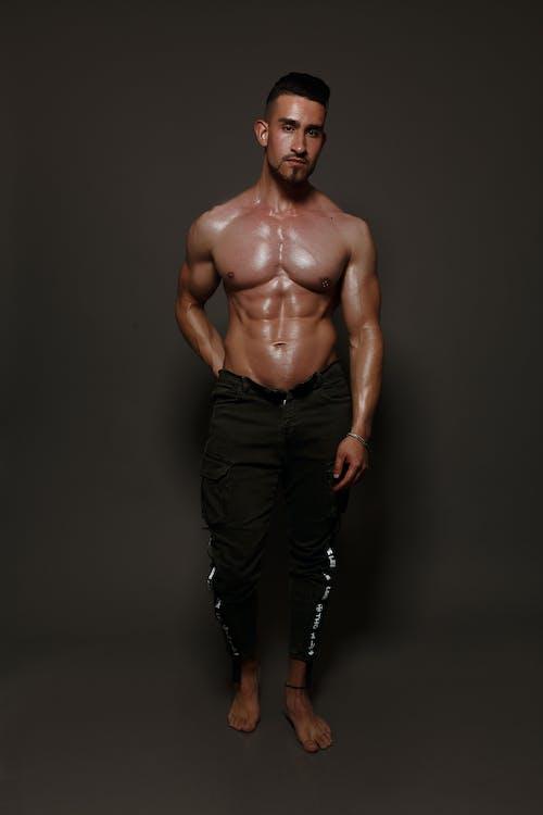 Muscular shirtless man on gray background