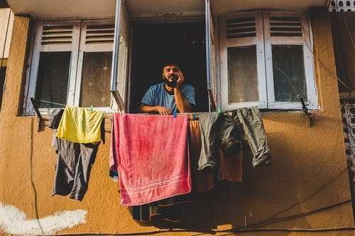 Man By An Open Window With Assorted Clothing Hanging On Clotheslines