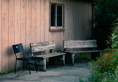 Two Gray Wooden Benches and Black Metal Armless Chair Beside Wall
