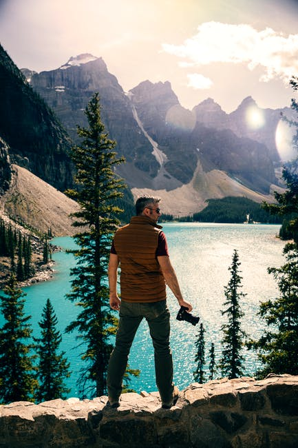 Man standing on a stonewall looking at the mountains and body of water