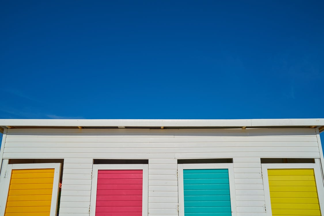 White Wooden House With Yellow, Pink, Green, and Orange Painted Windows