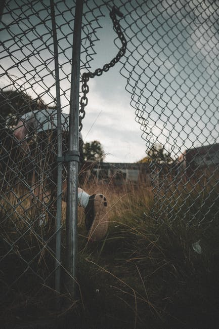 Person going through a broken wire fence