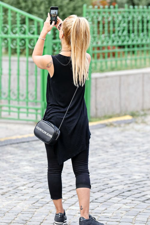 Woman Wearing Black Sleeveless Dress Holding Smartphone