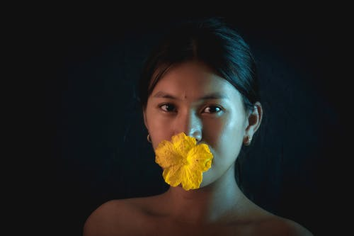 Woman With Yellow Flower on Her Lips