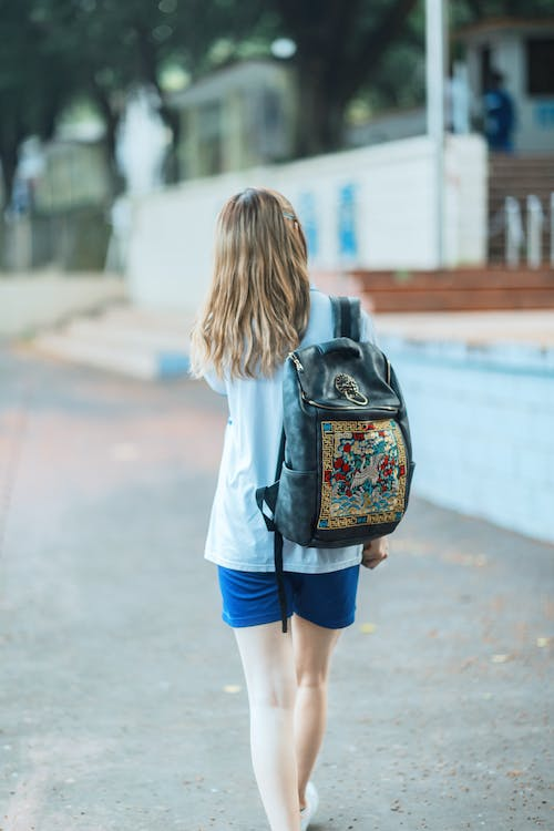Woman in White Shirt and Blue Shorts Carrying Backpack