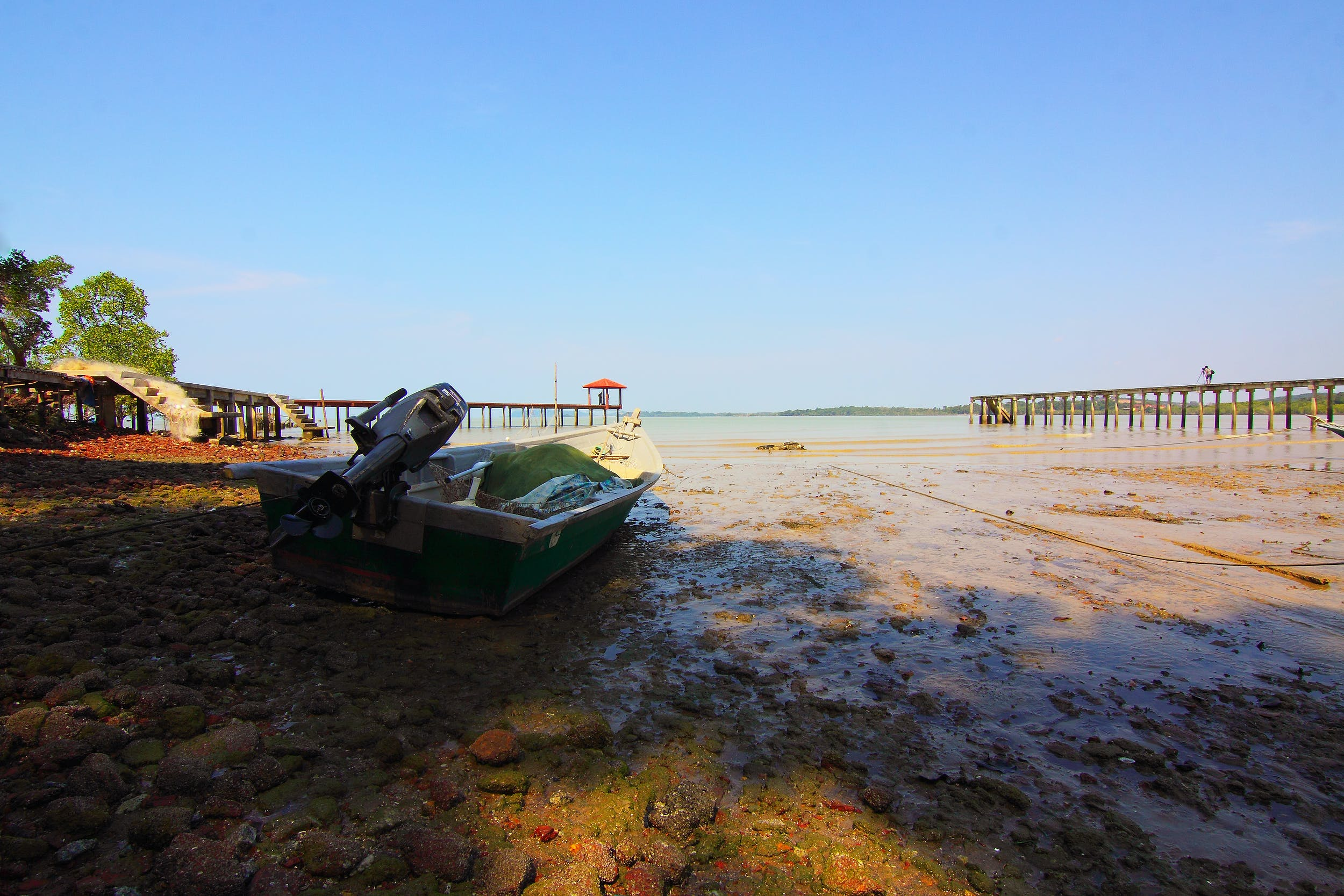 Boat With Outboard Motor on Seashore during Low Tide