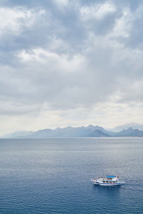 White Boat on Ocean Water during Cloudy Day