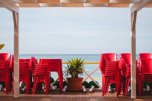Stacks of red plastic chairs on wooden terrace of cafe on seashore being closed