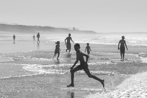 Kids running from sea waves on coast