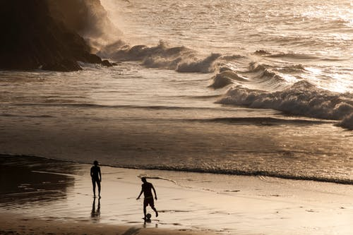 Men playing football on beach during sunset