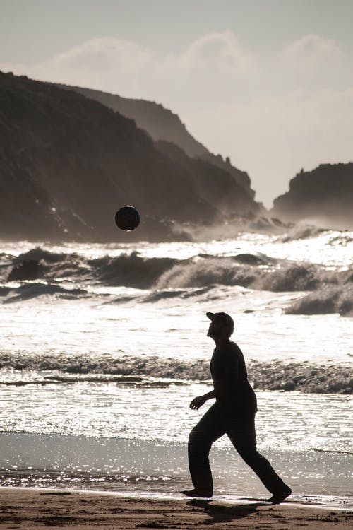 Side view full body of man running after ball on sandy coast along powerful stormy sea with cliffs on background