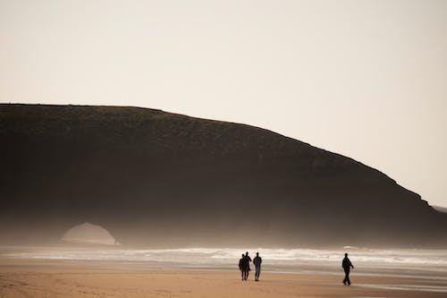 Traveling people walking along ocean beach