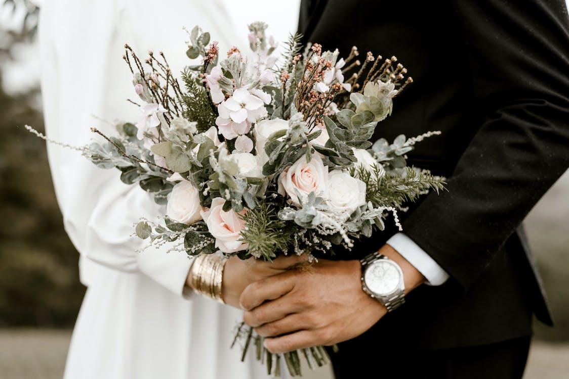 Pont Et Marié Debout Tout En Tenant Un Bouquet De Fleurs