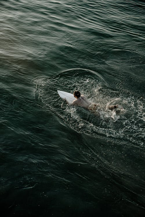Man Riding White Surfboard on Body of Water