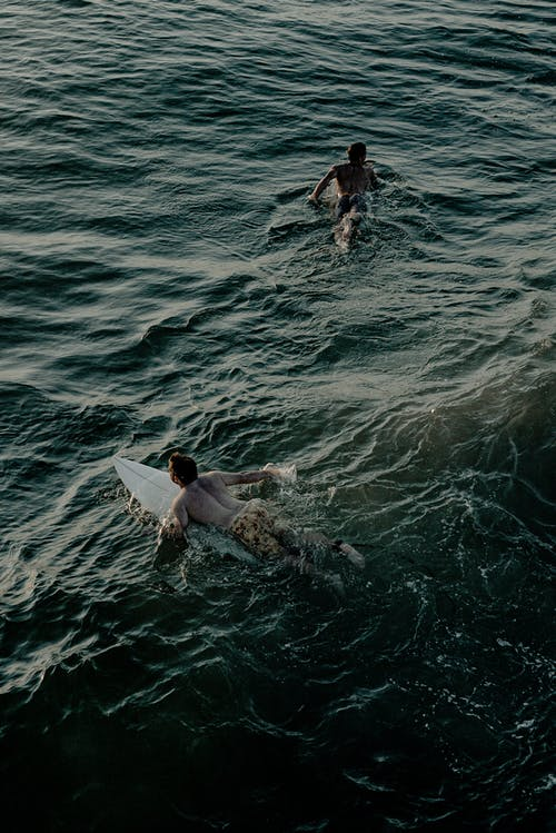 Photo Of People Surfing In The Ocean