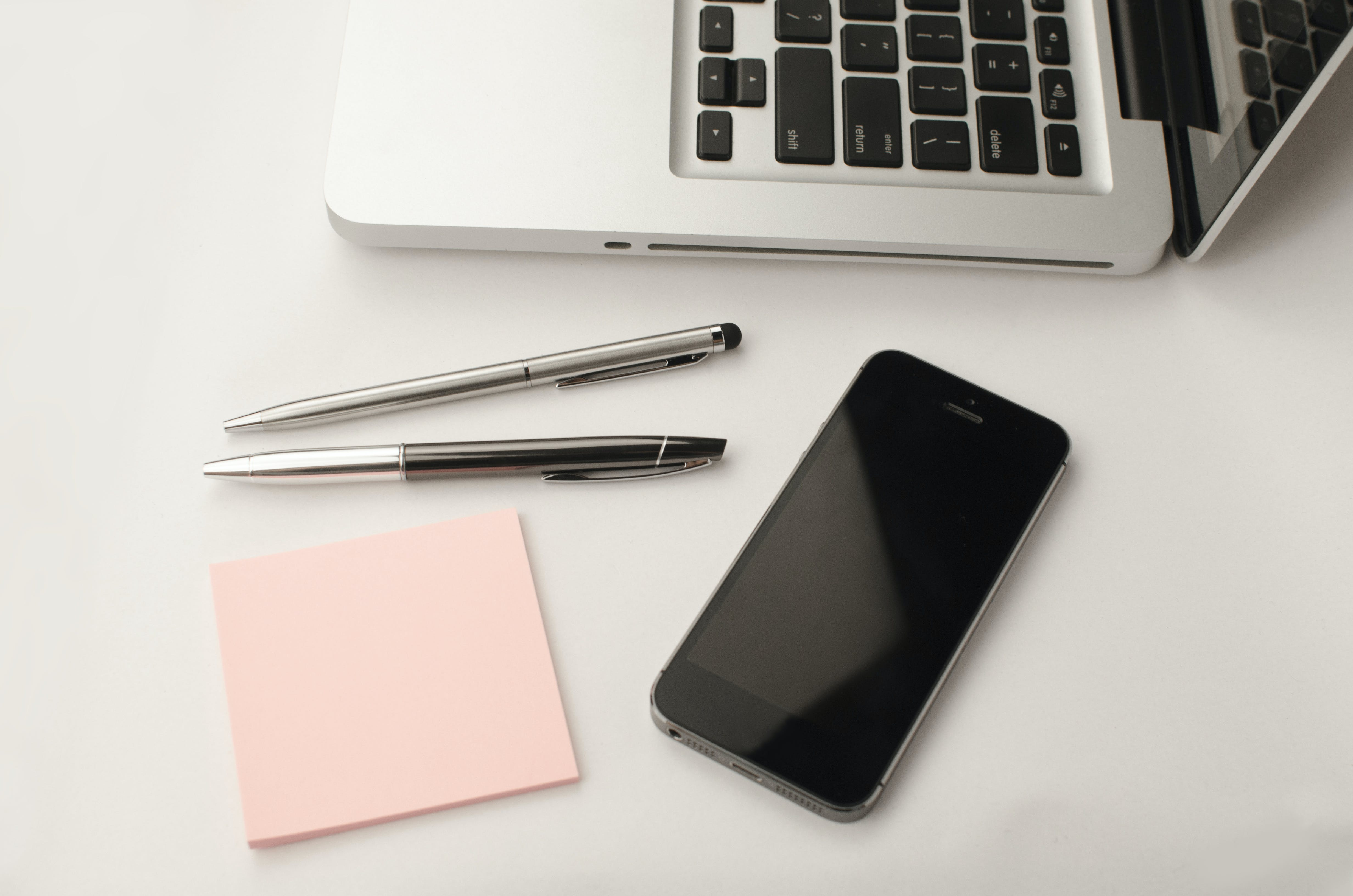 Space Gray Iphone 6 Beside Two Retractable Pens and Macbook