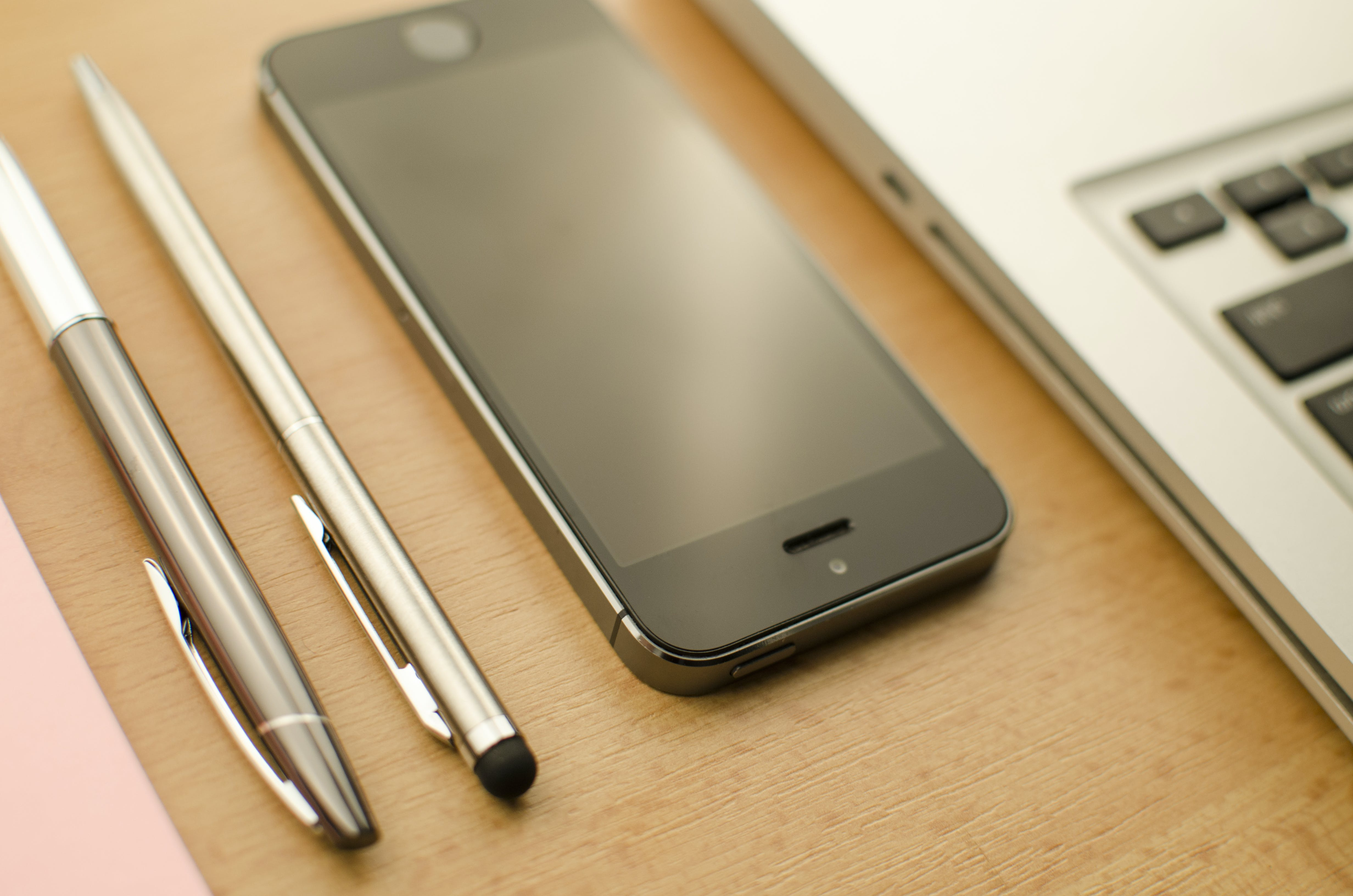 Space Gray Iphone 5s Beside Two Retractable Pens and Macbook