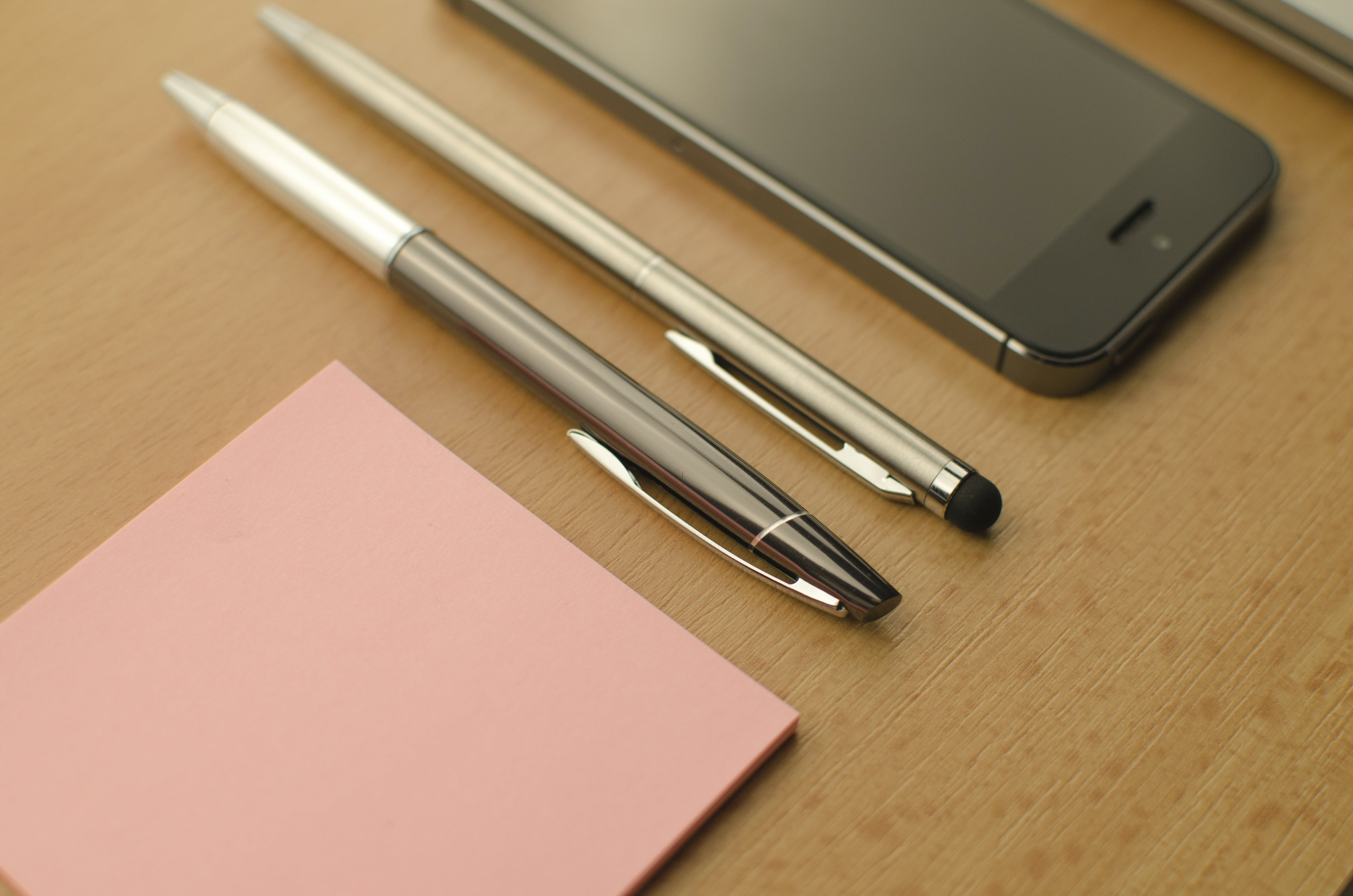 Two Click Pens Beside Iphone on Table