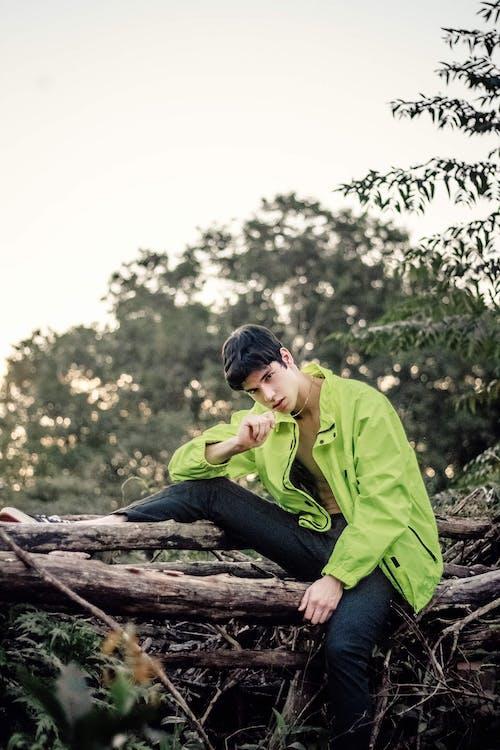 Man Sitting on Tree Log