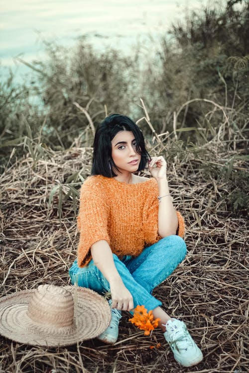 Woman Wearing Orange Knit Sweater and Blue Denim Jeans