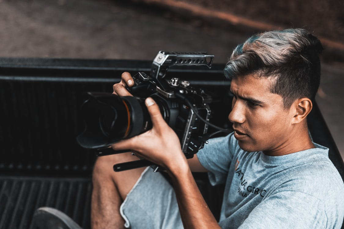 Man Wearing Gray Crew-neck Shirt and Gray Cargo Short Using Black Camera