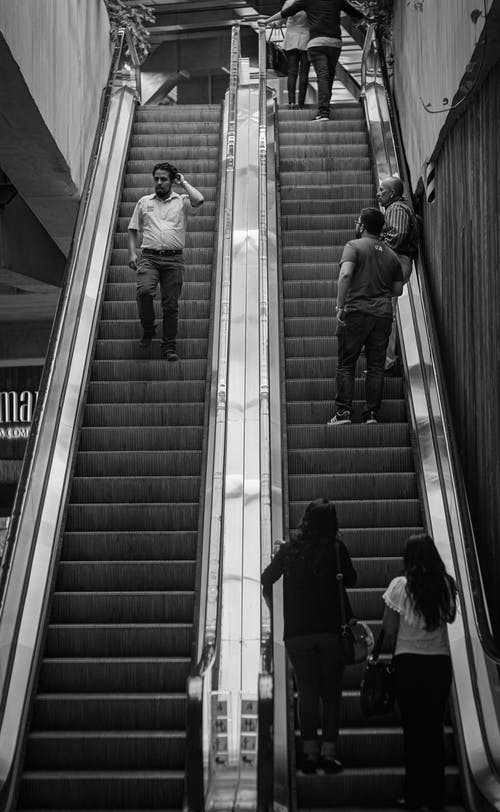 Grayscale Photography of People Riding Escalators
