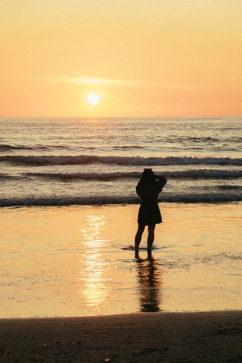 Silhouette Photo Of Woman Standing Beside Seashore