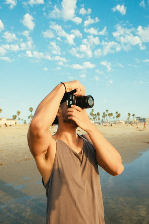 Man Using Dslr Camera While Standing on Seashore