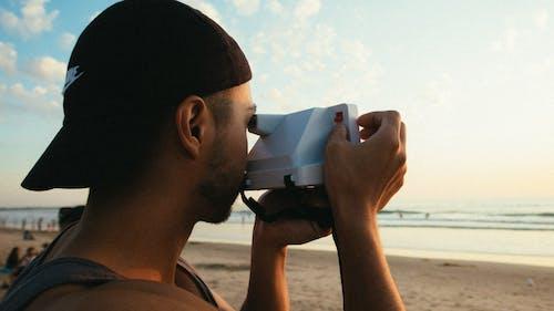 Immagine gratuita di berretto, macchina fotografica istantanea, mani, maschio