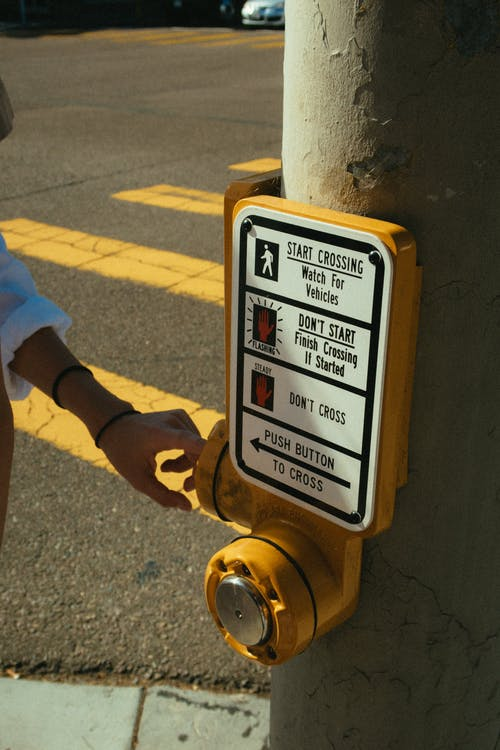 Photo of Person's Hand Near the Warning Sign