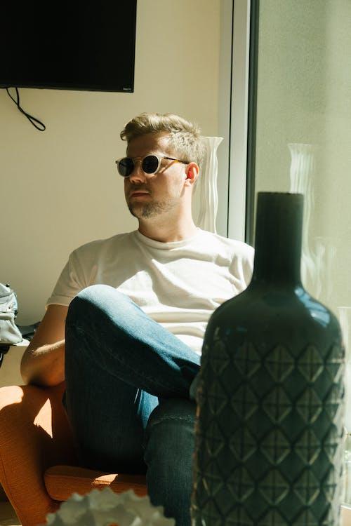 Foto d'estoc gratuïta de assegut, camisa blanca, gerro, home