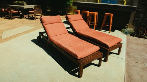 Two Brown Wooden Framed Outdoor Chaise Lounges