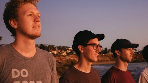 Three Men Wearing Crew-neck Shirt Standing Beside Beach