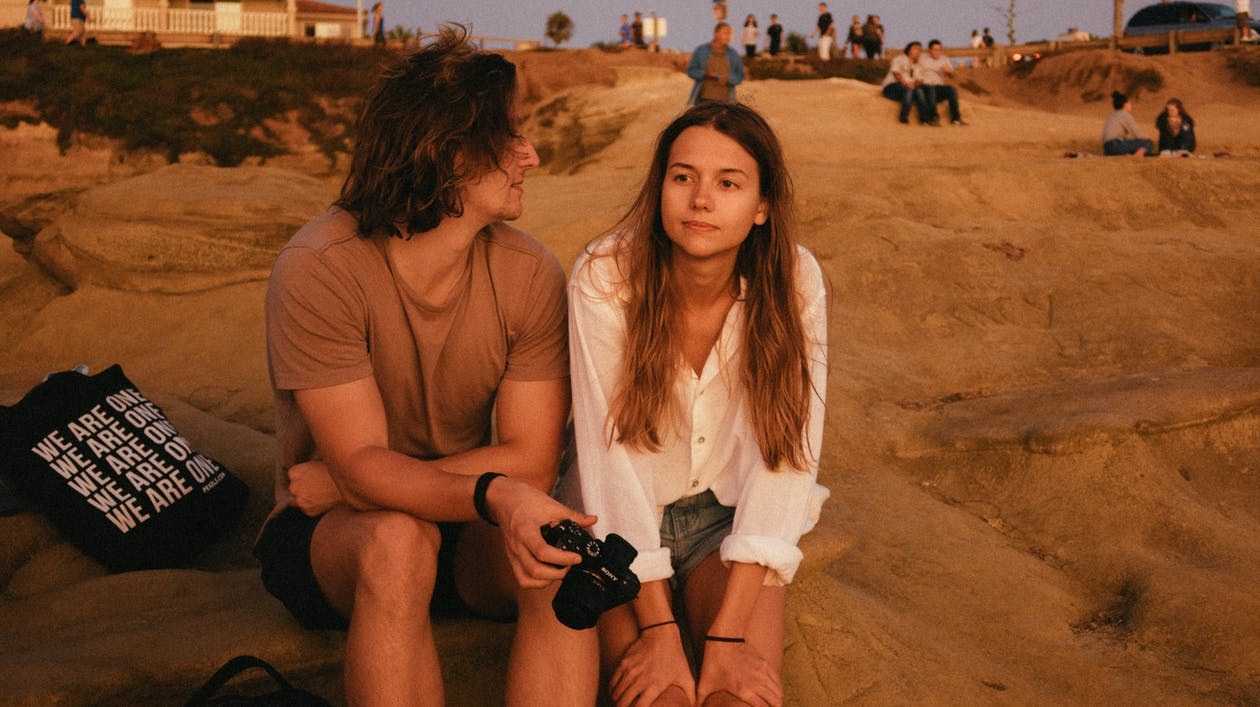 Photo of Man and Woman Sitting on Sand