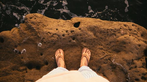 Person Standing On Cliff Wearing Brown Flip-flops