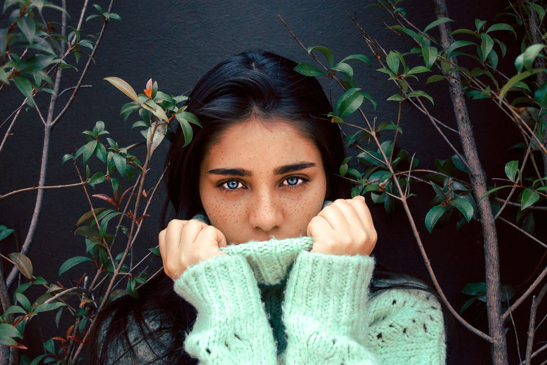 Woman Wearing Knitted Sweater Besides Green Plants