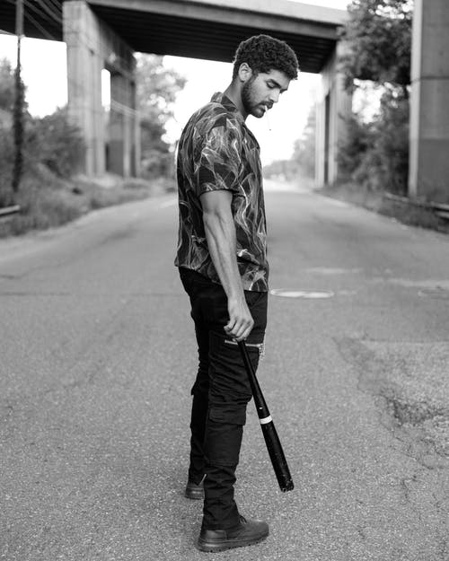 Man Standing on Road While Holding a Baseball Bat
