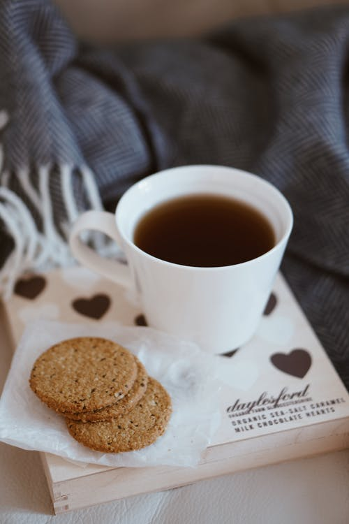 White Ceramic Coffee Cup Beside Biscuits