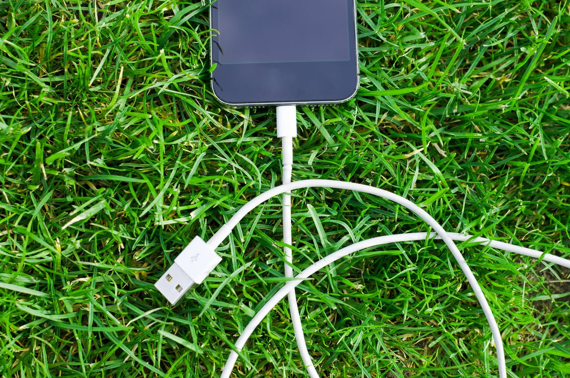 Black Ipod Touch and Cable on Grass