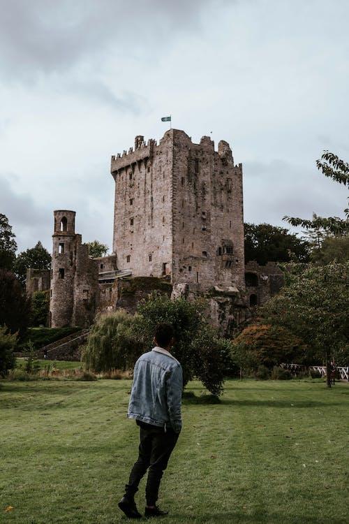 Man in Blue Denim Jacket Looking on Castle