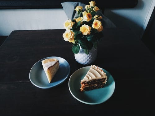 Two Sliced Cakes on Plates Beside Flowers